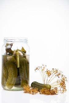In essig eingelegte gurken in einem glas auf einem weißen hintergrund