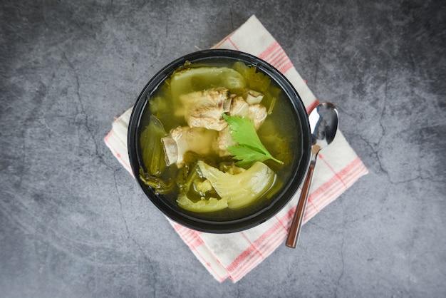 In essig eingelegte kopfsalatsuppe mit schweinerippchenknochensuppeschüssel mit gemüse