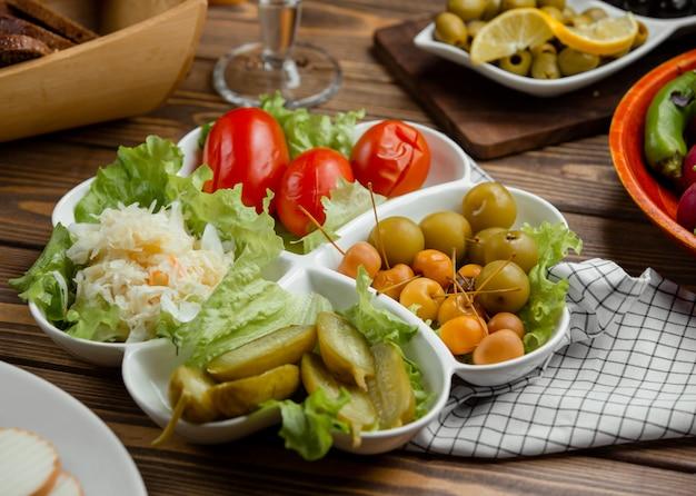 In essig eingelegte platte der gurke, der tomate, des kohls, der grünpflanze, der miniäpfel