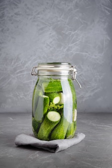 In essig einlegen und fermentationsgurke im glasgefäß mit dill und knoblauch auf dunkelgrauem