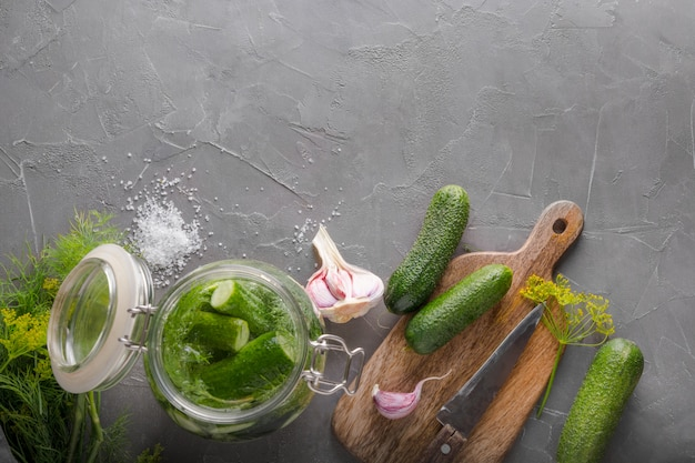 In essig einlegen und fermentationsgurke im glasgefäß mit dill und knoblauch auf grauer tabelle. ansicht von oben.