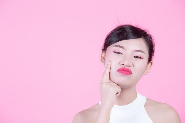 In facial skin problems women berührst unglückliche junge frauen ihre haut auf einem rosa hintergrund.