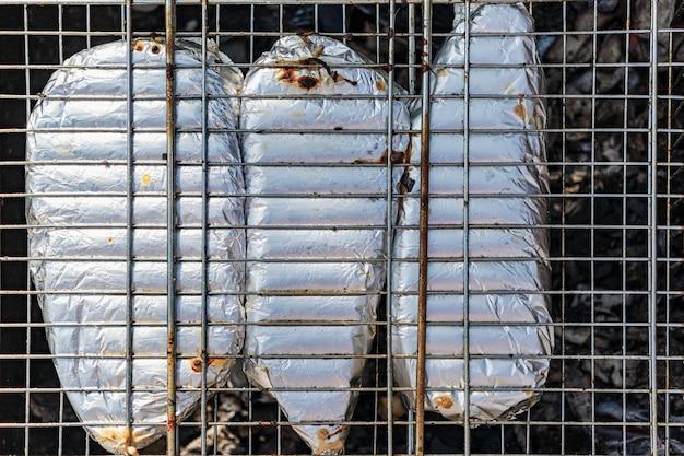 In folie gewickelter fisch auf dem grill. kochen von saftigem fisch über offenem feuer und kohlen.