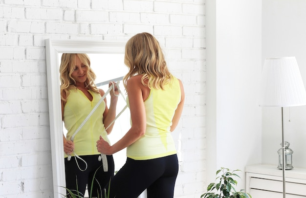 In form bleiben. attraktive frau mit dem athletischen körper, der geht, die taille mit einer maßart vor einem spiegel zu messen.