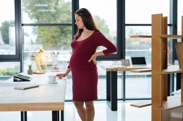 In gedanken. junge schwangere frau, die am tisch steht, während sie unten schaut und ihren