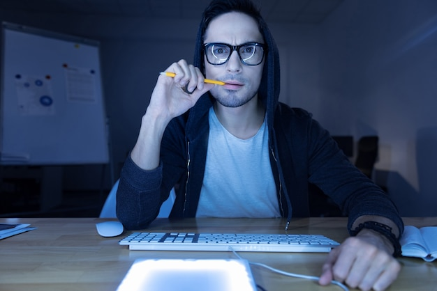 In gedanken verwickelt. hübscher genialer nachdenklicher hacker, der auf den computerbildschirm schaut und einen bleistift beißt, während er über seinen online-betrug nachdenkt