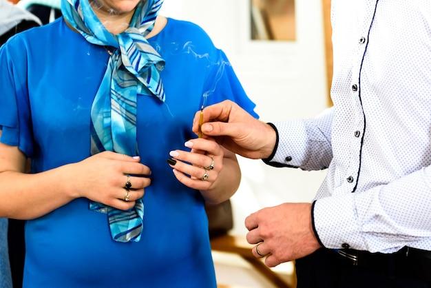 In händen halten kerzen und ein baby bei der taufe in der russisch-orthodoxen kirche.