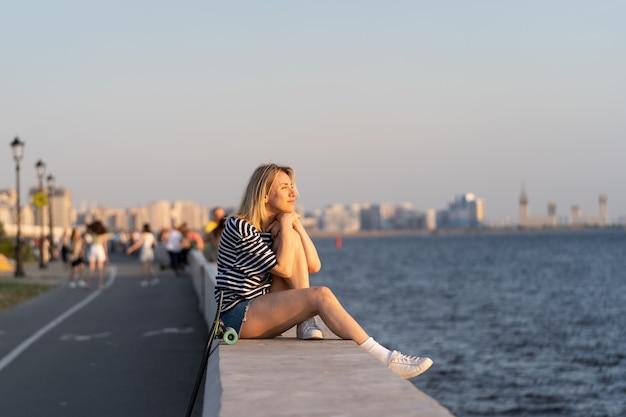 In harmonie mit sich selbst sitzt die frau allein am flussufer und genießt das konzept der freiheit bei sonnenuntergang im sommer