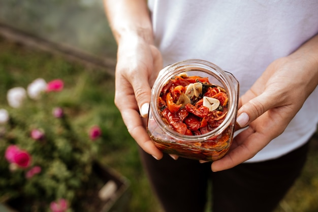 In ihrer hand befindet sich ein offenes glas mit sonnengetrockneten tomaten mit olivenöl.