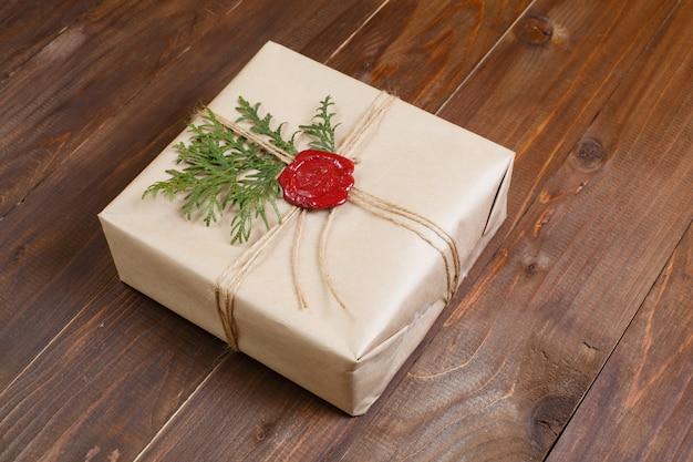 In kraftpapier eingewickeltes geschenk, mit schnur und geklebtem wachssiegel. liegt auf dem tisch.