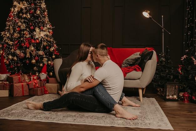 In liebe paar mann und frau sitzen auf dem boden mit gekreuzten beinen umarmen und küssen weihnachtsbaum