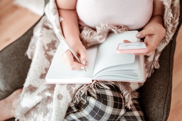 In notizbuch schreiben. gut aussehende frau im haushalt outfit füllen tagebuch mit metall slick pen