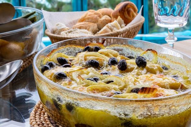 In olivenöl gebackener kabeljaufilet mit kartoffeln, brokkoli, gekochtem ei und schwarzen oliven. typisches gericht portugals.