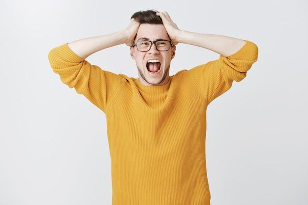 In panik geratener kerl, der alarmiert schreit und haare wirft