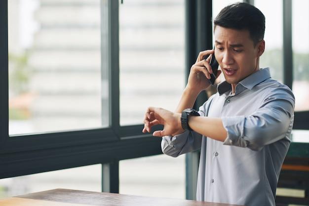 In panik versetzender asiatischer mann, der am handy spricht und armbanduhr betrachtet