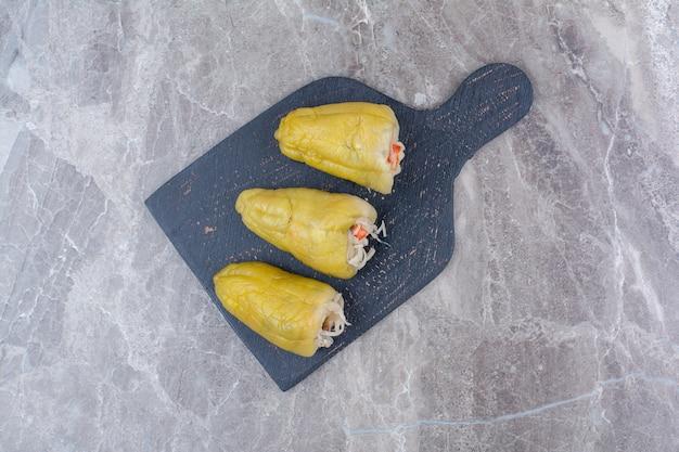 In paprika gefüllte gurken auf dunklem brett.