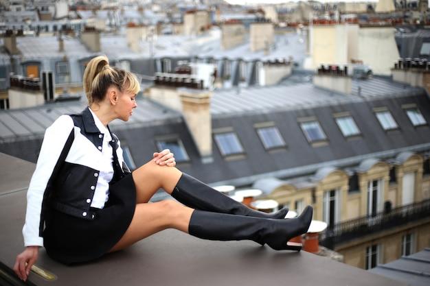 In paris sitzt eine schöne junge blonde frau in kurzen stiefeln mit hohen absätzen auf dem dach und schaut nach unten