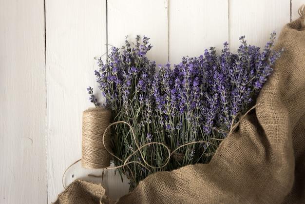 In sackleinen verpackter lavendel liegt auf dem tisch und ist in zierfaden gewickelt. draufsicht