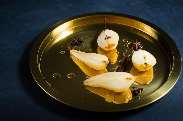 In scheiben geschnittene birne auf einem goldenen tablett pochiert, auf weißwein gekocht.