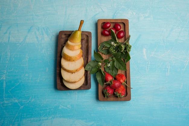 In scheiben geschnittene birnen mit erdbeeren und maulbeeren in holzplatten in der mitte