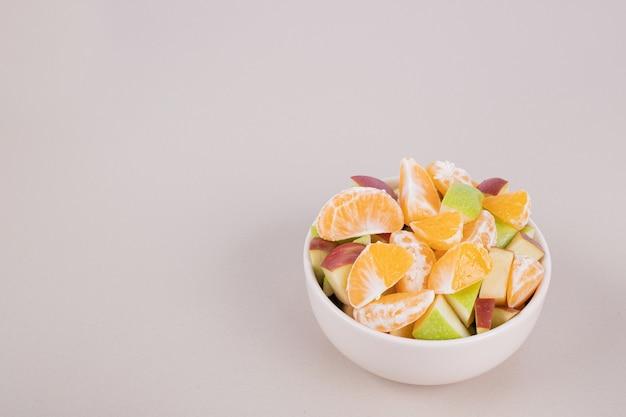 In scheiben geschnittene frische früchte in weißer schüssel.