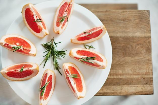 In scheiben geschnittene frische grapefruit und rosmarin auf weißem teller. von oben. gesunde fitness-diät-nahrung