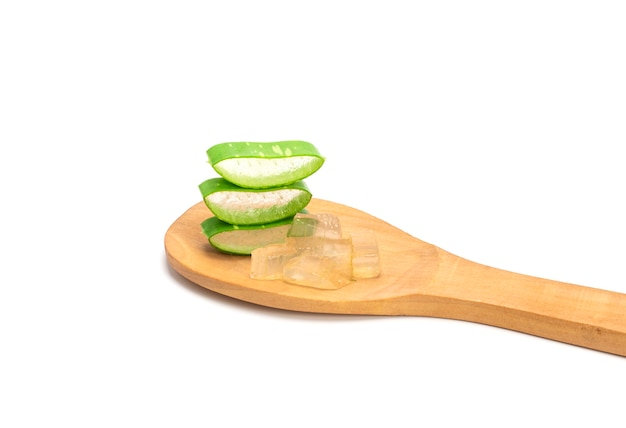 In scheiben geschnittene frische grüne aloe-blätter in holzlöffel isoliert auf weißem hintergrund. hautpflegekonzept, gesundheits- und schönheitsbad.