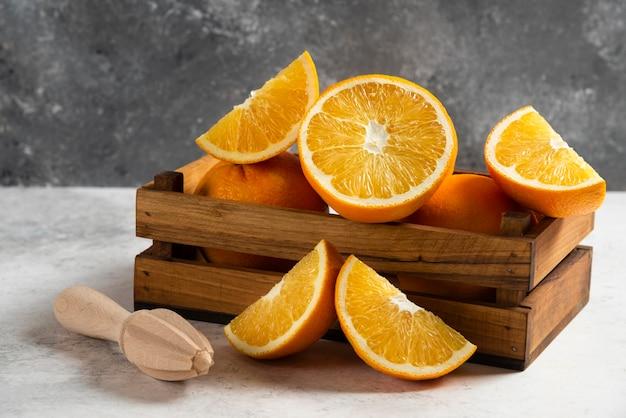 In scheiben geschnittene frische orangen mit holzreibahle auf marmor.