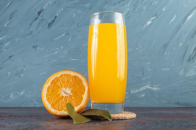 In scheiben geschnittene frische orangenfrucht mit blättern und einem glaskrug saft auf steintisch.
