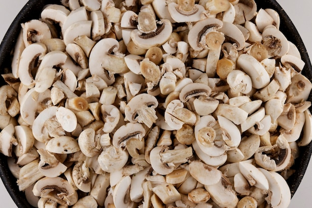 In scheiben geschnittene frische pilze in einen topf geben