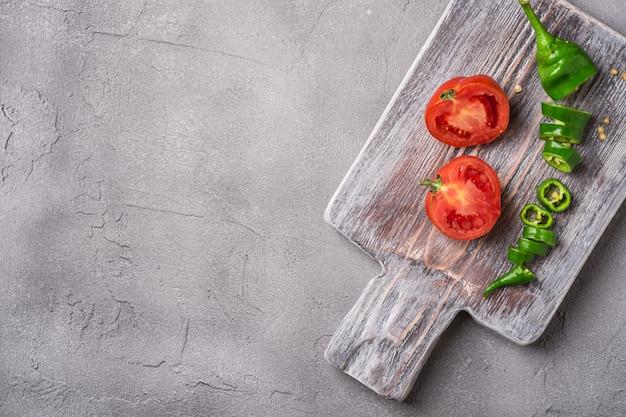 In scheiben geschnittene frische reife tomaten mit scharfen chilischoten auf altem holzschneidebrett