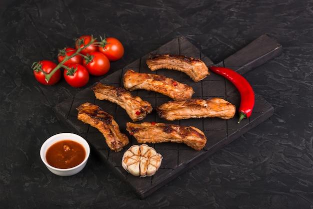 In scheiben geschnittene gebackene schweinerippchen auf einem dunklen brett mit paprika, knoblauch und roter sauce