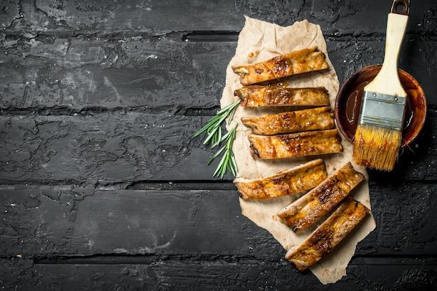 In scheiben geschnittene gegrillte rippen mit sauce. auf einem schwarzen rustikalen hintergrund.