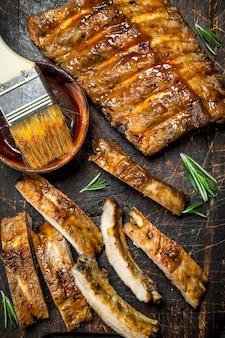 In scheiben geschnittene gegrillte rippen mit sauce.