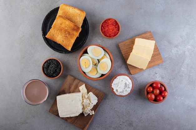 In scheiben geschnittene gekochte eier mit gebratenem toast und roten kirschtomaten.