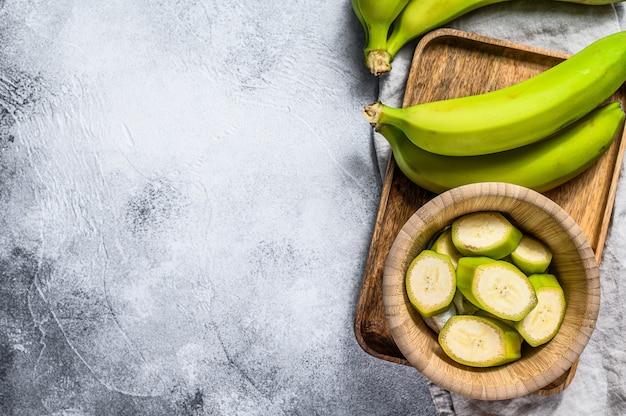 In scheiben geschnittene grüne banane in einer holzschale. draufsicht. tropische frucht