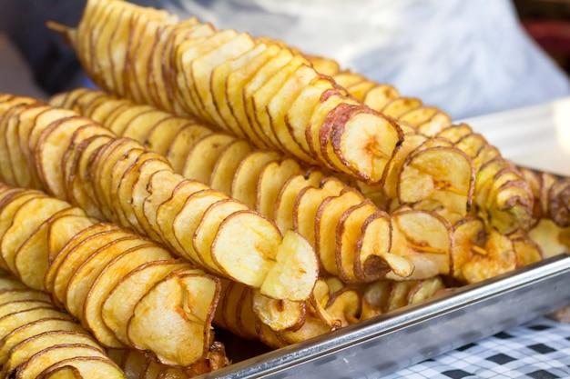 In scheiben geschnittene kartoffelchips auf einem dünnen holzstab.