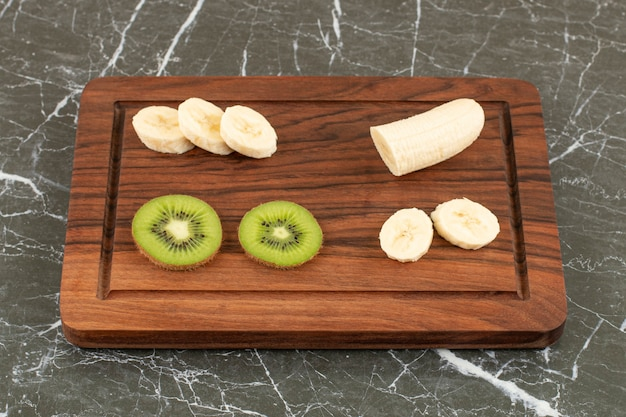 In scheiben geschnittene kiwi und banane auf holzbrett.