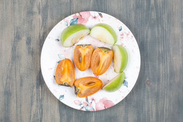 In scheiben geschnittene köstliche kaki mit geschnittenem grünem apfel
