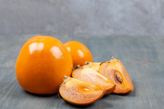 In scheiben geschnittene köstliche persimone in einem holztisch