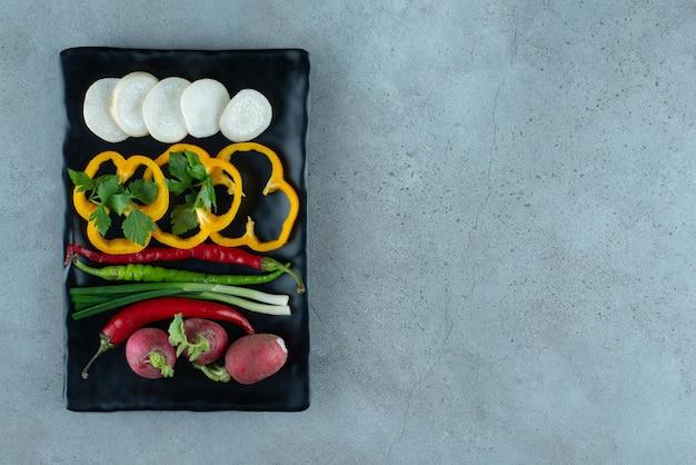 In scheiben geschnittene paprika, rüben, gemüse und zwiebeln auf schwarzem teller.