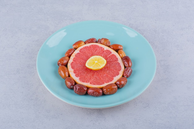 In scheiben geschnittene reife grapefruit, zitrone und silberbeeren auf blauem teller.