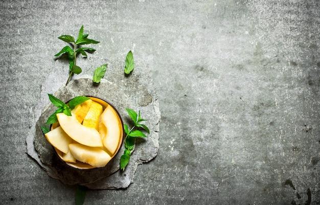In scheiben geschnittene reife melone mit minzzweigen.