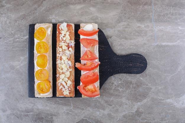 In scheiben geschnittene reife und unreife tomaten auf knusprigem brot auf dem schneidebrett, auf dem marmorhintergrund.