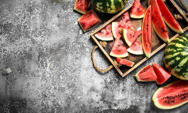 In scheiben geschnittene reife wassermelone auf holztablett auf rustikalem tisch.