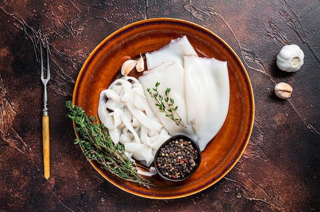 In scheiben geschnittene rohe ringe tintenfisch in einem rustikalen teller mit rosmarin