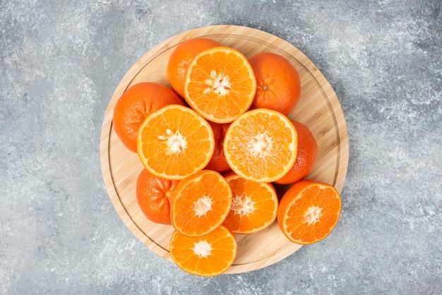 In scheiben geschnittene saftige frische orangenfrüchte in einem holzteller.