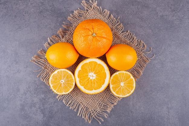 In scheiben geschnittene saftige orange und zitrone auf steinoberfläche gelegt.