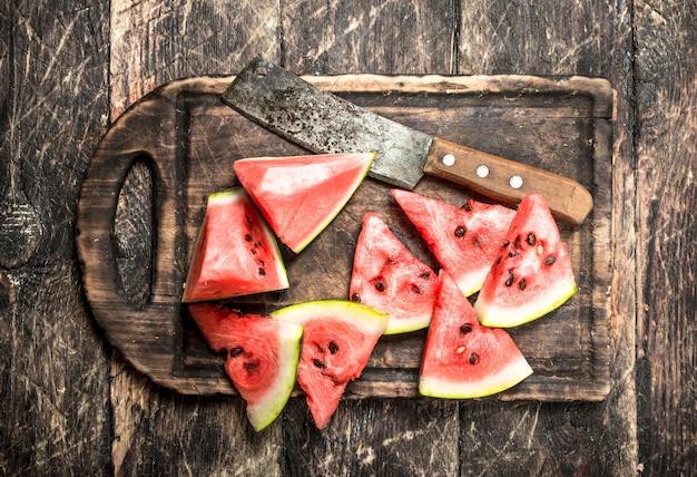 In scheiben geschnittene scheiben reifer wassermelone auf holztisch.