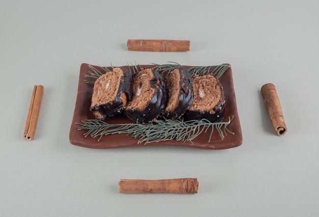In scheiben geschnittene süße schokoladenrolle mit zimtstangen.